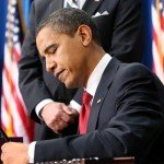 Obama signing a bill
