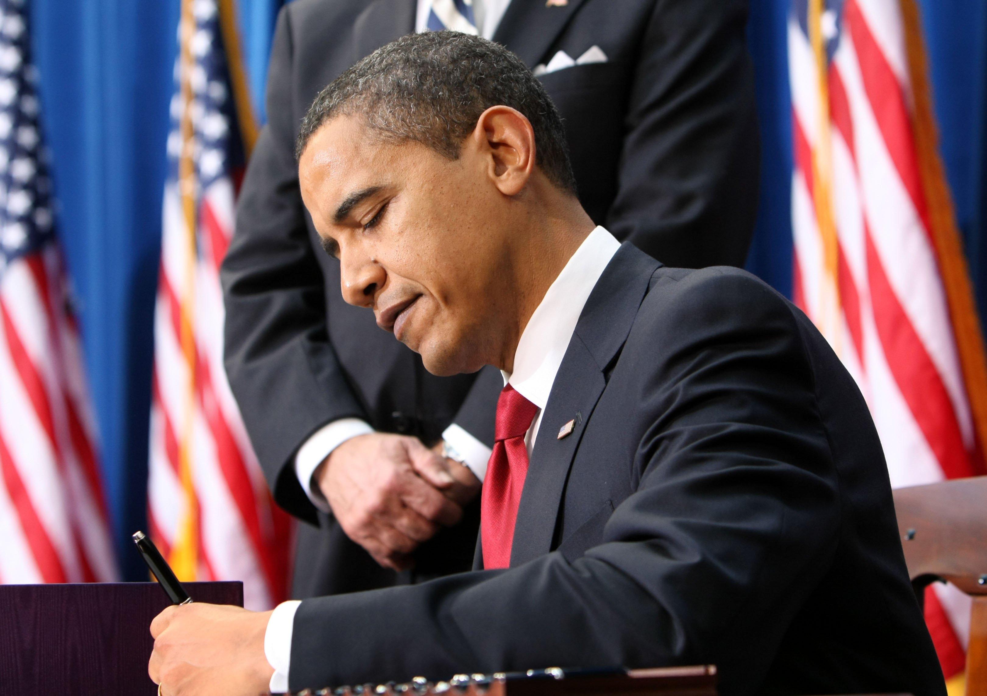 Obama signing a bill